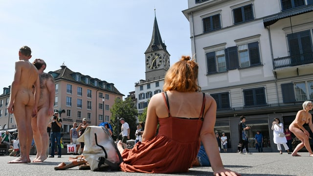 Angezogene Frau sitzt am Boden und betrachtet zwei nackte Männer.
