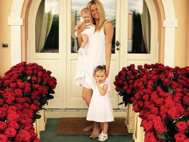 Michelle Hunziker mit einem Baby auf dem Arm und einem Mädchen neben ihr stehend. Alle drei tragen weisse Kleidchen. Links und rechts von ihnen sind rote Rosen zu sehen.