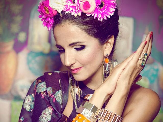 Eine schöne Frau mit Blumen in den Haaren und viel Schmuck an den Handgelänken.