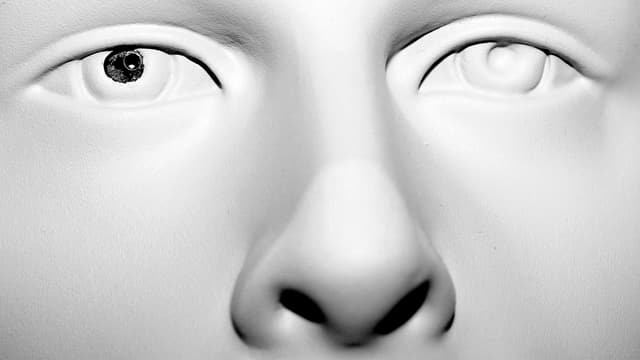 Weisse Maske, bei der ein Auge ausgestochen und durch eine kleine Spionage-Kamera ersetzt worden ist.
