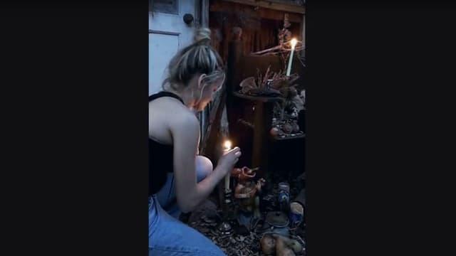Ein Mädchen zündet vor einer Hütte eine Kerze an.