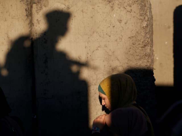 Palästinenserin in der Altstadt von Jerusalem, dahinter der Schatten eines Soldaten.