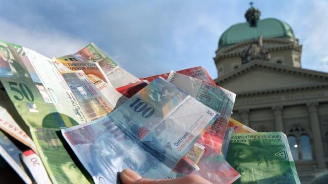 Eine Person hält einen Bündel Geld vor dem Bundeshaus.