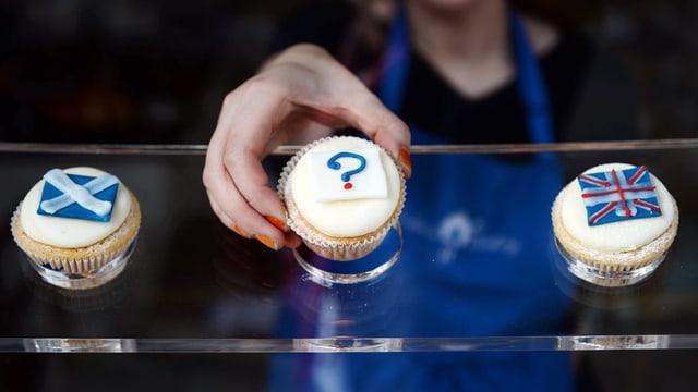 Trais muffins en ina conditoria. Tgenin prender, quel cun la bandiera scozzesa ni quel cun la britannica? Entamez il segn da dumonda.