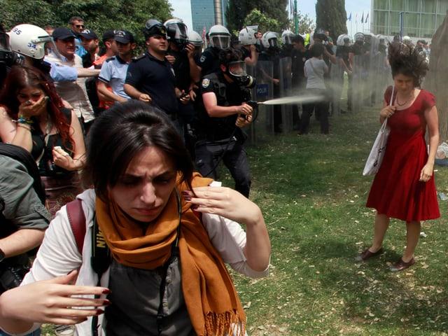 Ein türkischer Polizist setzt einen Pfefferspray gegen eine Demonstrantin ein.