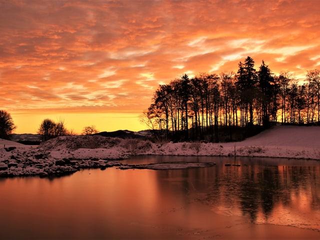 Oranger Himmel, See im Vordergrund.