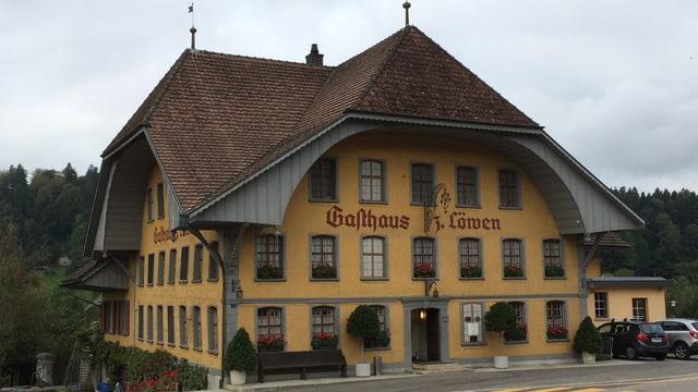 Der markante Gasthof mit gelber Fassade und grauen Dachbögen.