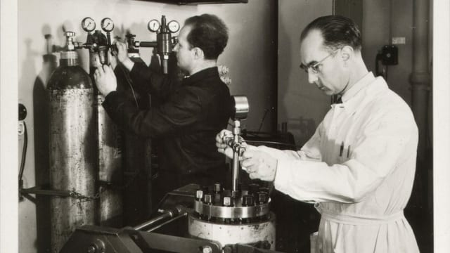 Schwarz-weiss-Bild eines Mannes in einem weissen Kittel, der konzentriert an einer Art Maschine steht.