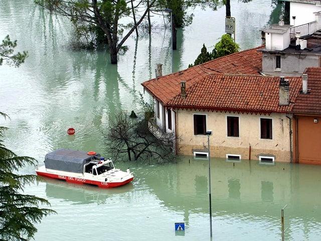 Ein Schwimmfahrzeug plügt sich durch das Hochwasser in einem italiensichen Ort