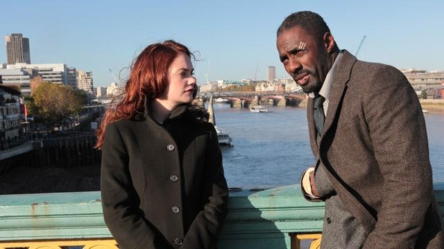 Der Schauspieler Idris Elba und seine Schauspielkollegin Ruth Wilson lehnen an einem Brückengeländer