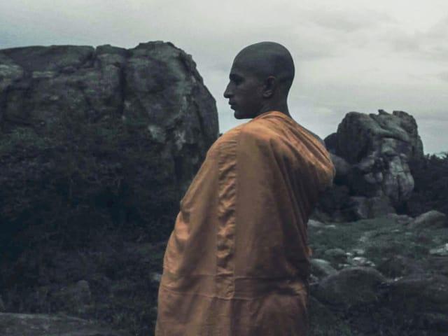 Ein Mann, gekleidet in einem orangen Umgang, steht in der Natur und blickt auf die Seite. Er ist umgeben von Felsen und Steinen.