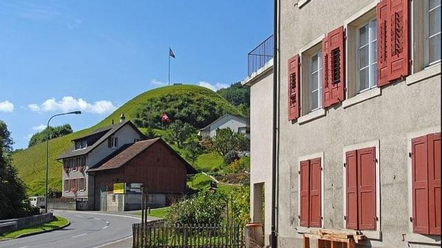 Strasse durchs Dorf mit Hügel und Fahne