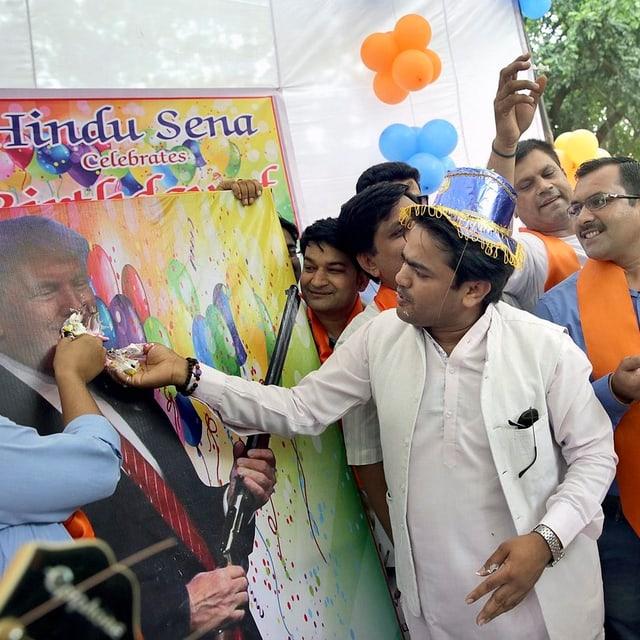 Eine Gruppe von Indern füttert ein Trump-Plakat mit Kuchen.