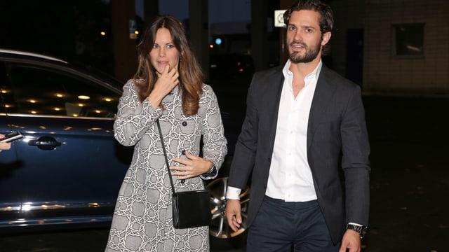 Sofia Hellqvist in einem graugemusterten Mantel und Carl Phillip in einem schwarzen Anzug verlassen ihre Limousine und laufen in eine Konzerthalle.