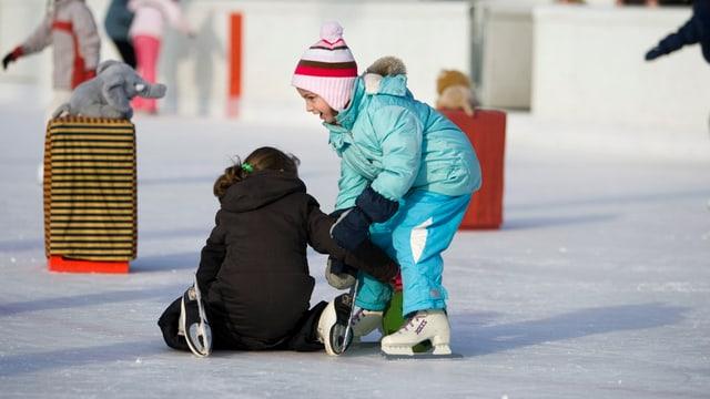 Spielende Kinder auf dem Eisfeld der Sportanlage Heuried in Zürich-Friesenberg.