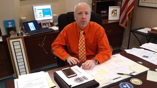 Ein Mann in orangem Hemd sitzt an einem Schreibtisch.