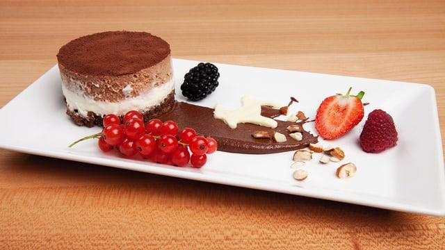 «Gääs-Törtli» mit Beeren ausgarniert auf einem weissen rechteckigen Teller.