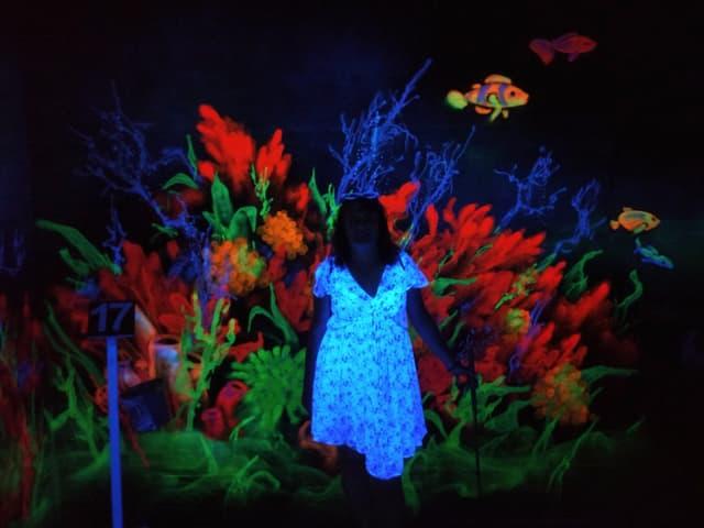 Farbenspiel im dunklen Keller mit Frau im Vordergrund.