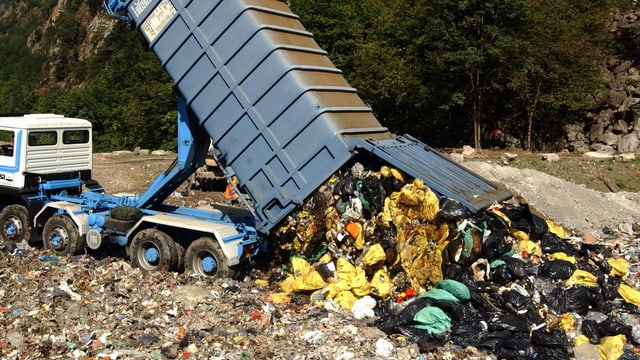 Lastwägen lädt Müll in Deponie ab.