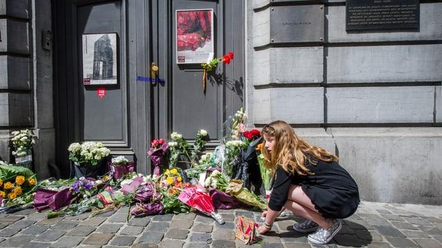 Ein Mädchen legt vor dem Museum eine Blume nieder.