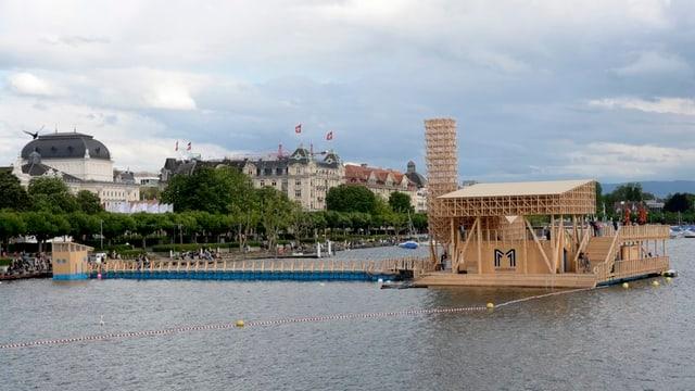 Am rechten Bildrand schwimmt ein Floss aus hellem Holz auf dem See. Daneben sieht man die hohen Gebäude des Zürcher Seefeld. Auf einem Haus ragen zwei Schweizer Flaggen in die Höhe.