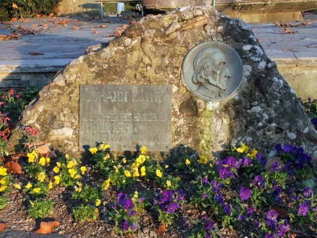 Tafel und Porträit auf einem Felsen in einem Blumenbeet.