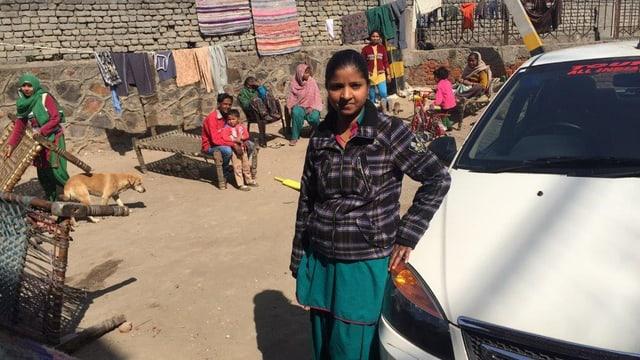 Savita, angelehnt an ihr Taxi, hinter ihr Einwohner von Delhi.