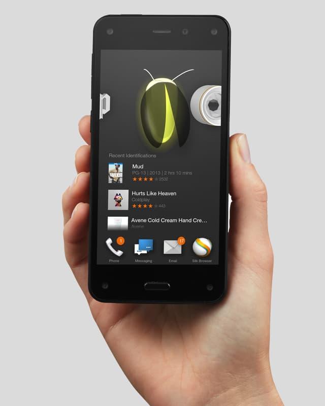 Eine Hand hält ein Fire Phone mit der Firefly-Funktion in die Höhe.