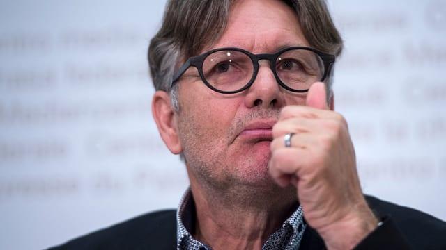 Hanspeter Thür bei einer Medienkonferenz, hält linken Daumen nach oben.