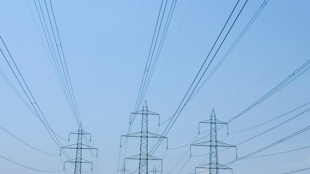 Starkstrommasten und Leitungen, im Hintergrund blauer, wolkenloser HImmel