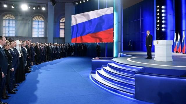 Putin steht auf Bühne, vor ihm Publikum.