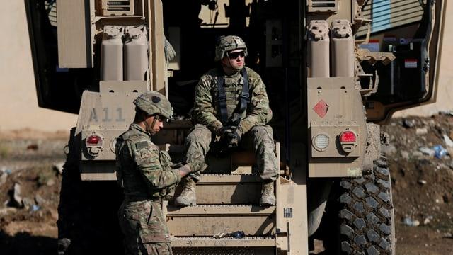 US-Soldaten auf einem Panzerwagen sitzen.