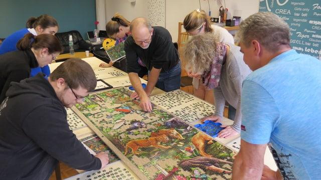Acht Leute bücken sich über das Puzzle auf einem langen Tisch.