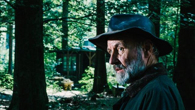 Ein Mann mit Hut steht im Wald vor einer Hütte
