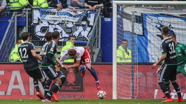 Ein Fussballer schiesst mit dem Rücken zum Tor.