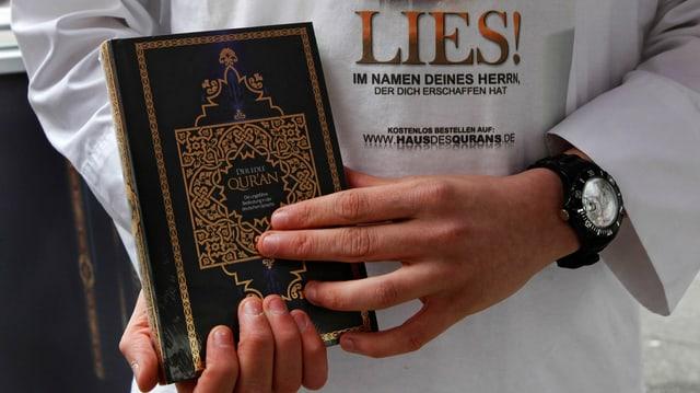 Ein Salafist hält ein Exemplar des Korans.
