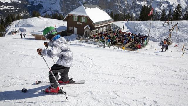 Kind auf Skiern auf einer Skipiste, im Hintergrund ein Restaurant mit voller Sonnenterrasse.