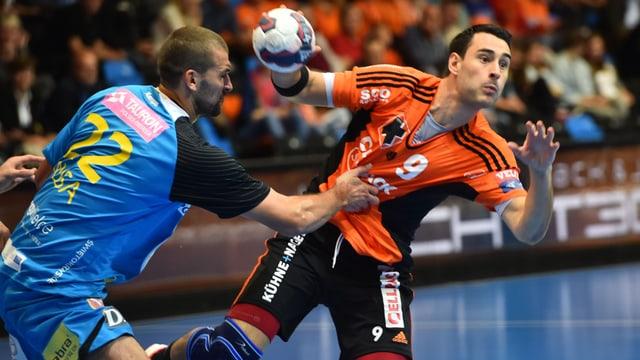 Handball-Spieler im Zweikampf.