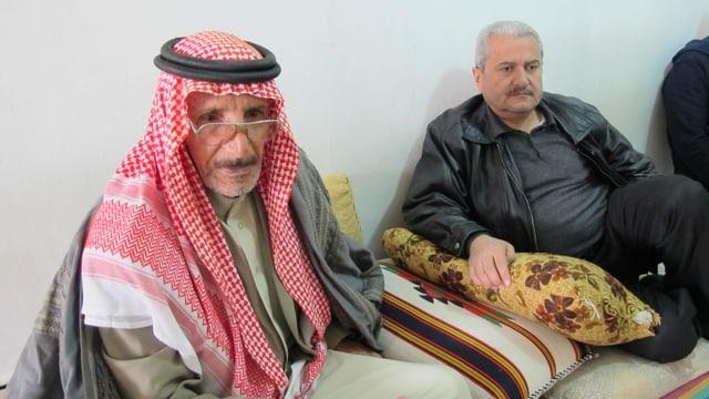 Zwei Männer sitzen auf Kissen am Boden. Einer trägt ein Tuch als Kopfbedeckung.