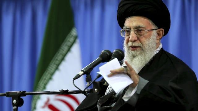 Khamenei mit schwarzem Turban spricht in ein Mikrofon, hinter ihm blaue Vorhänge.
