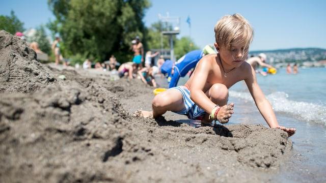Ein kleiner Bub spielt am Ufer des Zürichsees im Sand