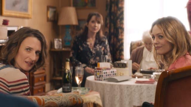 Tisch in einem Wohnzimmer, an dem vier Frauen unterschiedlichen Alters sitzen