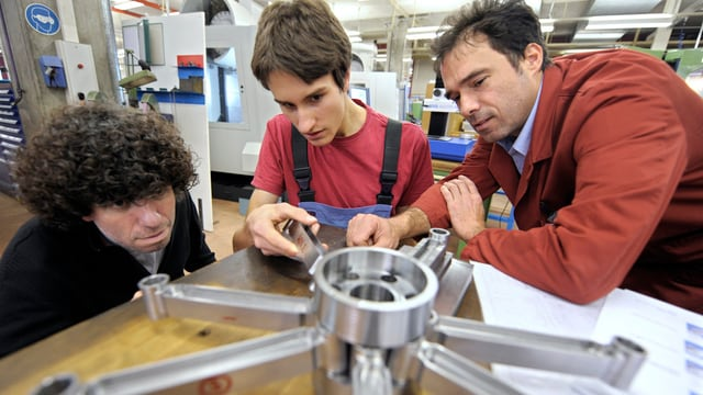 Zwei Lehrmeister und ihr Lehrling an einem Metallstück.