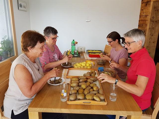 4 dunnas preparan la salata da tartuffels per la tschaina da la festa dil vitg.