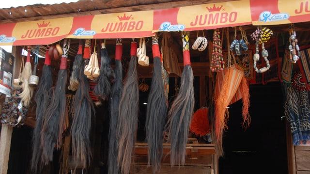 Voodoo-Zubehör – Haare, Ketten, Armringe und kleine Trommeln – an einem Marktstand.