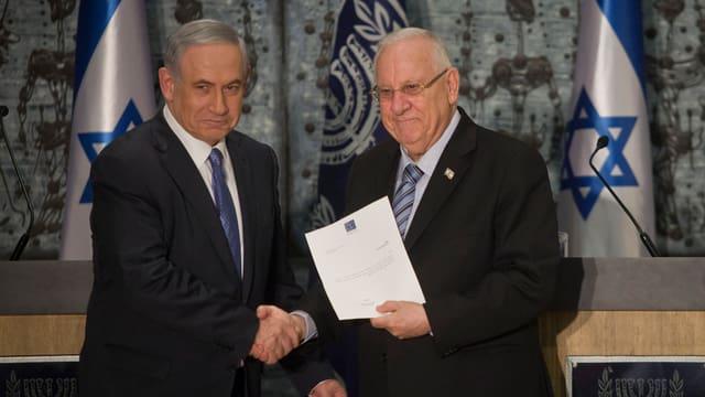 Benjamin Netanjahu (links) bekommt vom israelischen Staatspräsidenten Reuven Rivlin (rechts) ein Dokument überreicht.