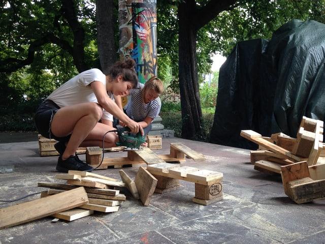 Zwei junge Frauen schleifen mit einem Gerät Holzpaletten ab.