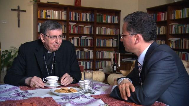 Ein katholischer Würden träger und ein Mann im Anzug sitzem am Tisch und trinken Kaffee.