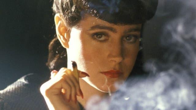 Filmszene: eine Frau raucht eine Zigarette und schaut in die Kamera