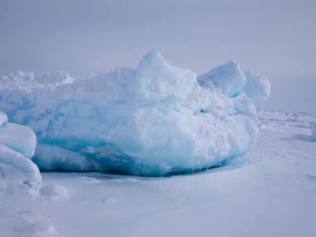 Ein Eisbrocken, der unten grosse blaue Einlassungen hat.